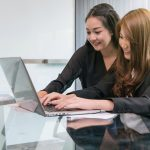 Two Asian young Businesswoman sitting and using the technology laptop in the modern workplace, Business lifestyle and technology concept