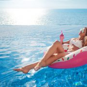 Summer Vacation. Enjoying suntan Woman in bikini on the inflatable mattress in the swimming pool with coctail.